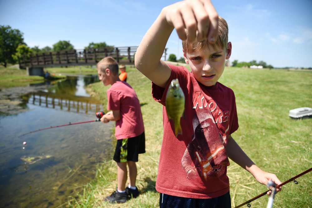 Caden Creuzer, 9, holds a fish he caught while fishing with his summer school class at Lake Montesian in Monticello June 24, 2016. Creuzer, who goes to Abraham Lincoln Elementary, likes to fish with his uncle and catfish are his favorite to catch.