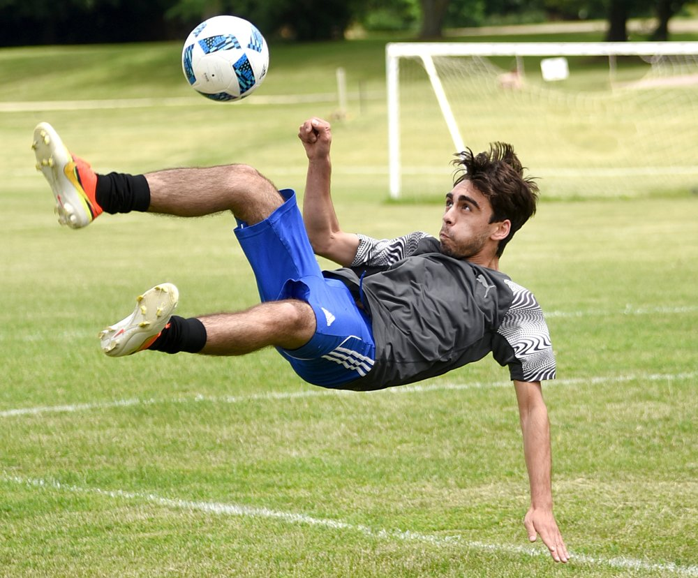Giacomo Zerilli does a bicycle kick during a pickup soccer game behind the Green County Family YMCA June 28, 2016.