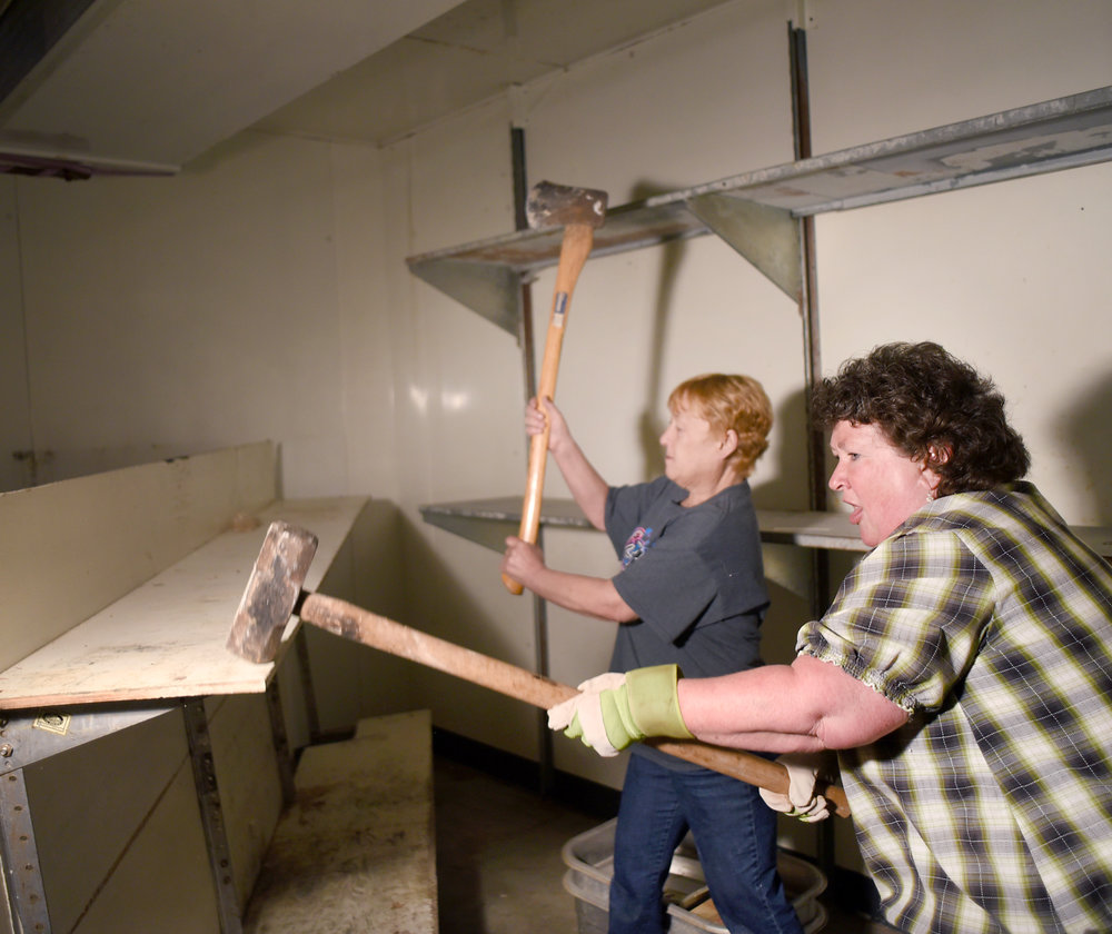 Laurie Hanson, of Argyle, and Muffy Rhyner, of Lake Geneva, try to break apart an old shelf during the renovation of Belle's Argyle Grocery on April 21, 2016.