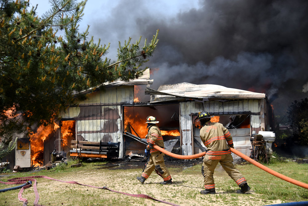 Monroe firefighters work to extinguish a fire that destroyed a storage shed on Pond View Road May 22, 2016. The shed was fully engulfed when firefighters arrived. Owner George Mau said he has owned the building since 1991 and used it to store collectibles he has been accumulating for almost 60 years.