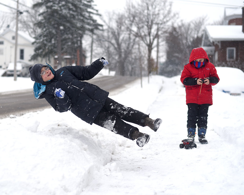 Malaki Cooter, 9, jumps into a pile of snow while his brother, Kayden Cooter, 6, tries to drive a remote controlled car on the sidewalk outside their home in Monroe Dec. 11, 2016. The brothers were enjoying the snow and made several snow angels.