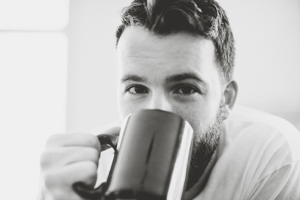 Daniel Adam holding coffee mug black and white