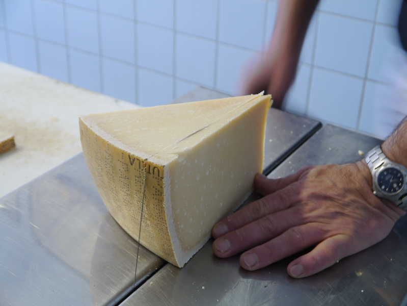 In Parma, the cheesemaker cuts us a fresh piece of Parmigiano-Reggiano to try.