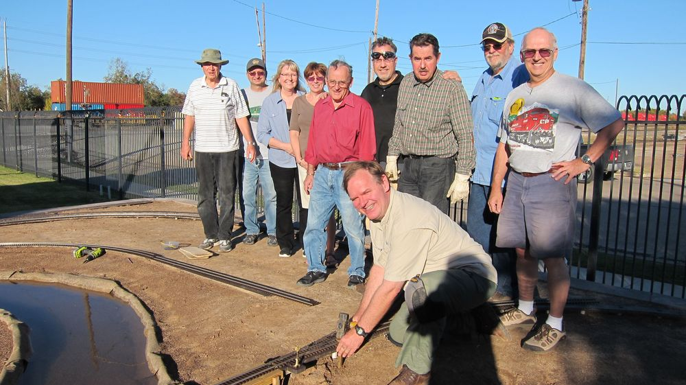 Greg Cauthen, member of the RMM Board and HAGG member, drives the Golden Spike.  RRM Board President Bill Rickert (2nd from left) joins with other members of HAGG to celebrate this much-anticipated milestone! :-)