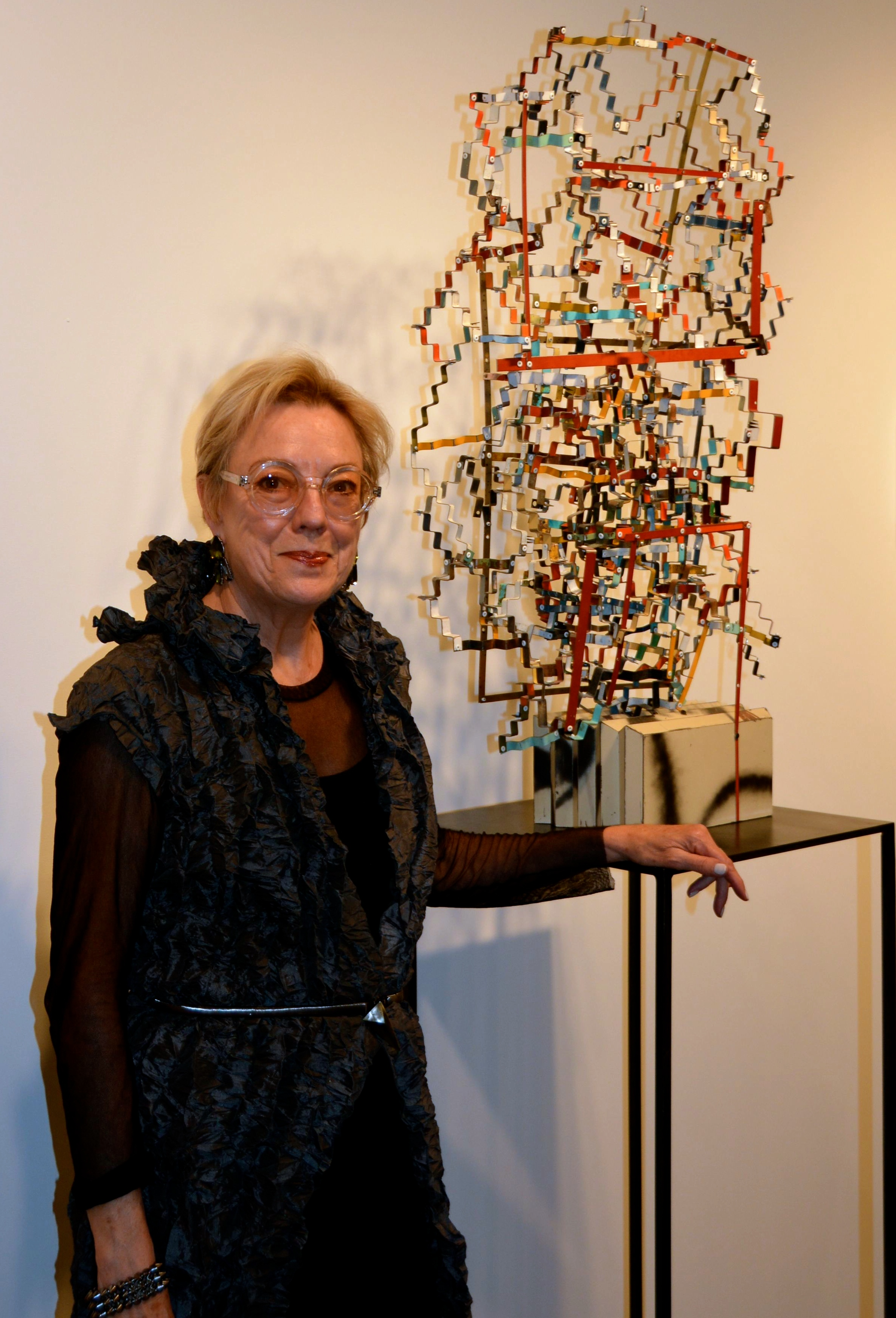 "Nancy Whiteneck of Conduit Gallery standing next to Ted Larsen's salvaged metal sculpture, ""Pure Evil"""