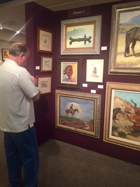 A collector studies a Joe Beeler (1931-2006) oil on canvas estimated at $4,000-$6,000