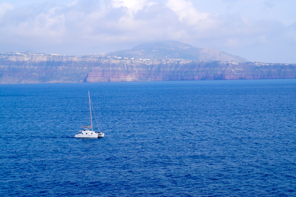 Sailboat in Santorini with the cliffs in the distance.
