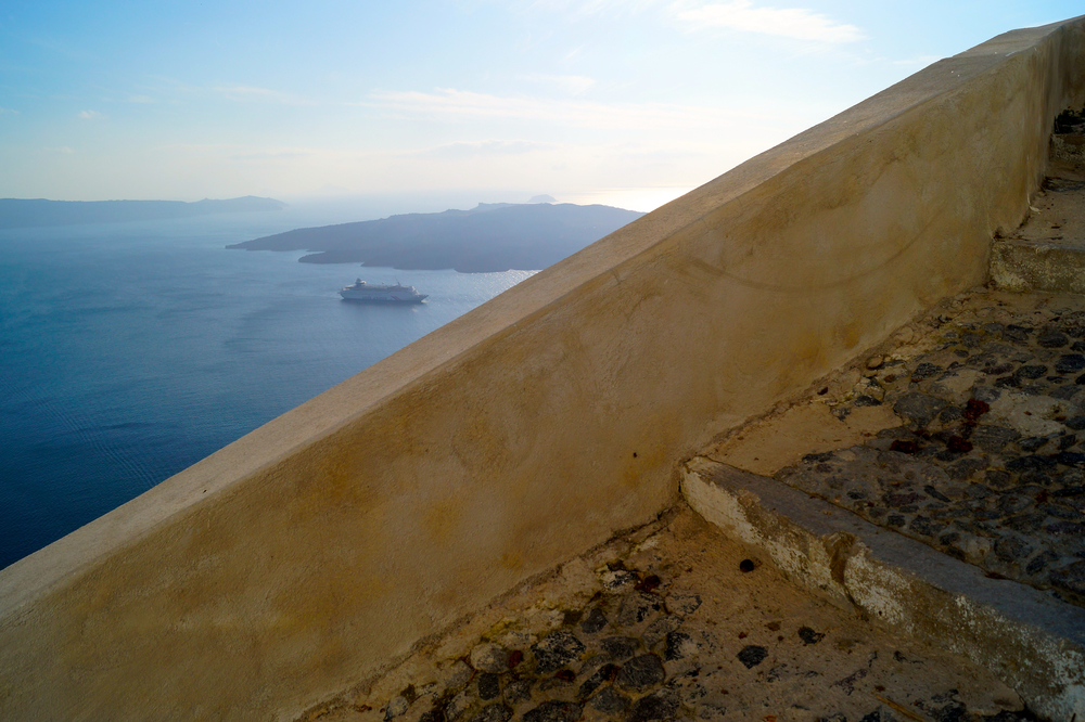 The stairs on the cliffs looking out over the Sea with the volcano and cruise ship next to it.