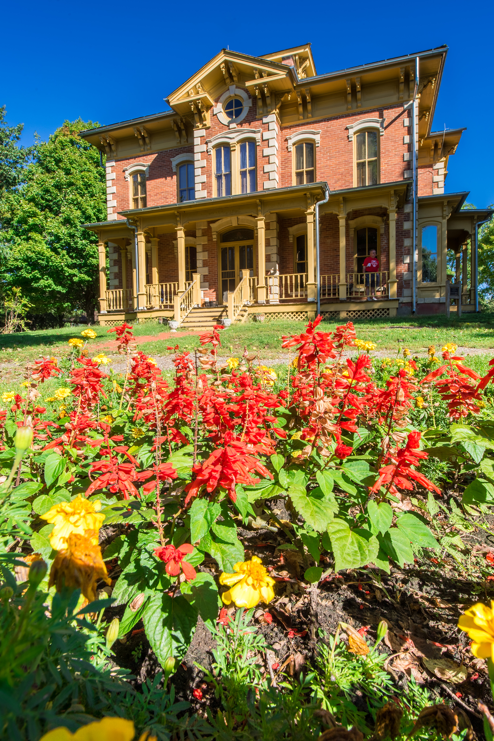 Outside the mansion shot from the garden with the bright red and yellow flowers.