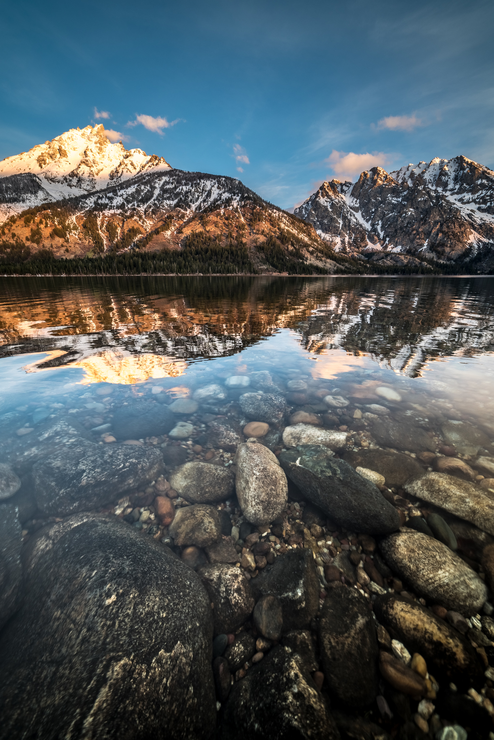 A vertical composition showing off how clear the water is in Jenny Lake as the morning sun kisses the peak of Grand Teton.