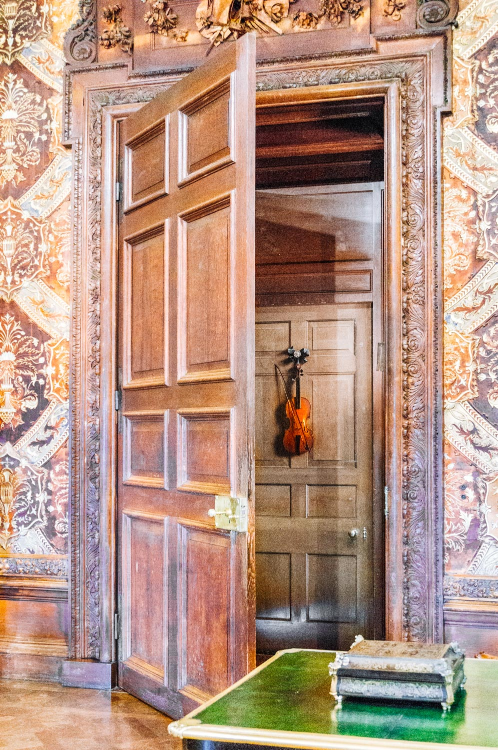 Trompe-l'oeil of a violin and bow on a real door. This 17th century painting was rescued from a fire in London and brought to Chatsworth in the 18th century