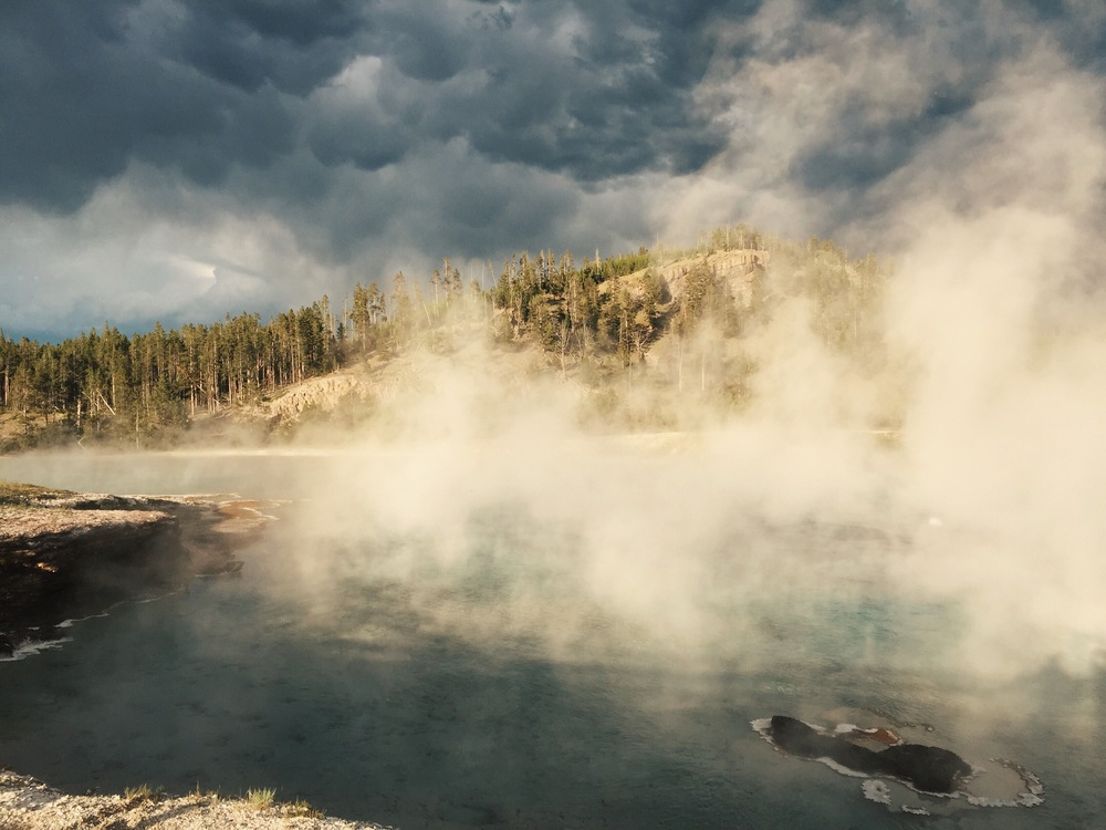Watching the thunderclouds roll in as the sun shines moody light on the steamy Excelsior Geyser in Yellowstone National Park.
