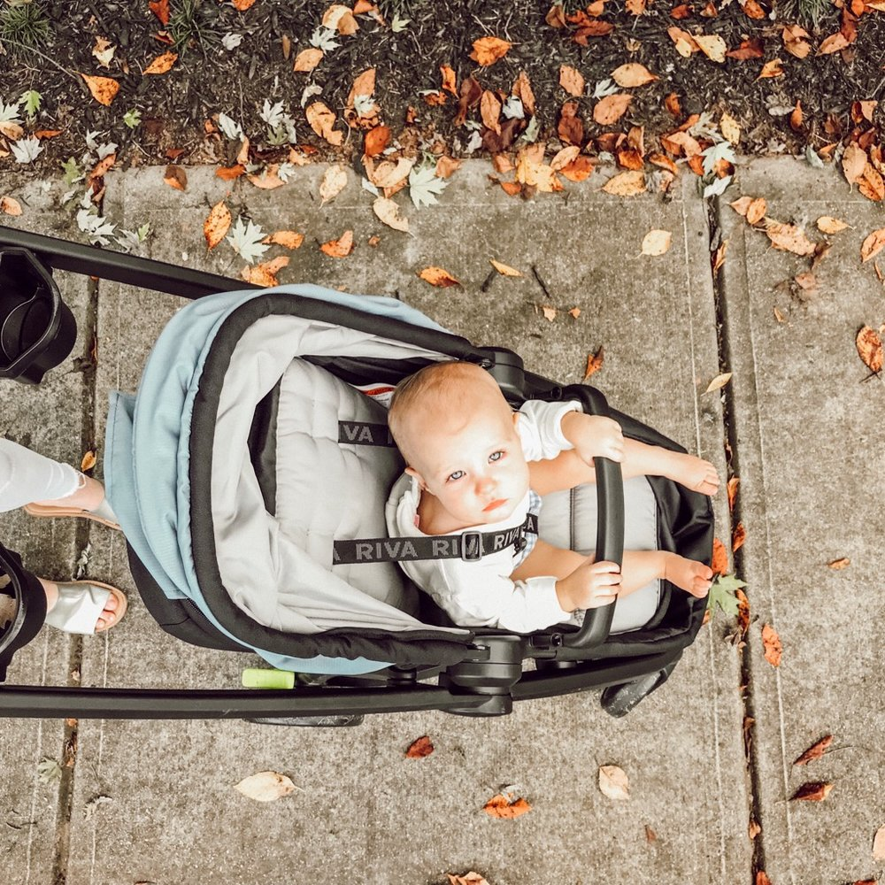 safety first stroller with baby girl on walk in fall