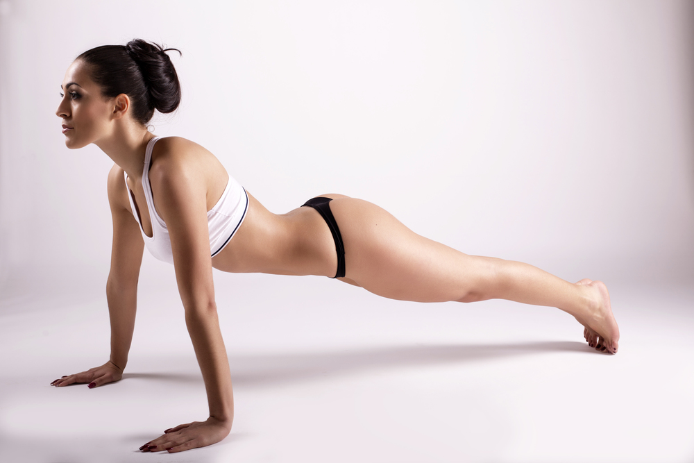 The plank pose in yoga fires up your core, opens up your shoulders, and tones your sides and your butt, creating unbelievable fitness and sexiness at the same time.