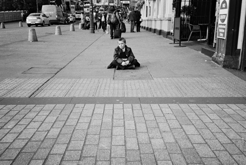 This kid was just sitting in the middle of the sidewalk with his lunchbox and a look of boredom on his face. Shot on Olympus XA and Kodak Tri-X 400.