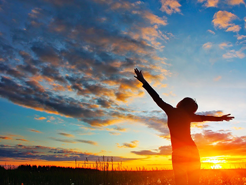 Woman-Outstretched-Arms-Sunset.jpg