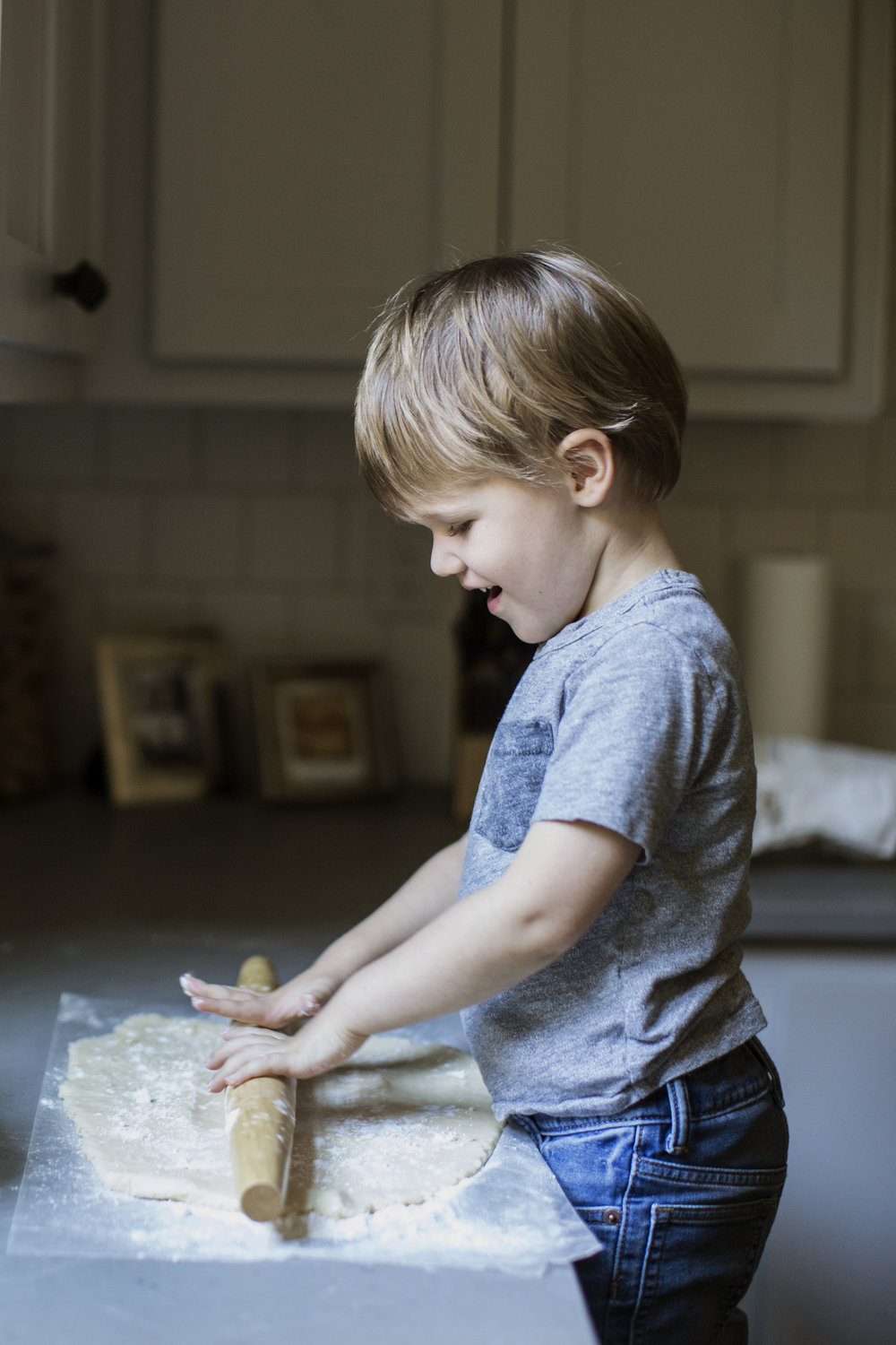 child rolling dough