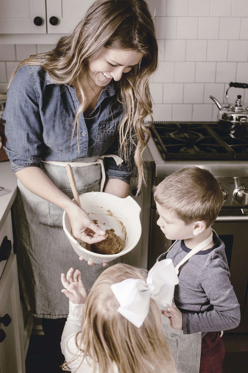 kids tasting dough with mom in the kitchen  / heirloomed