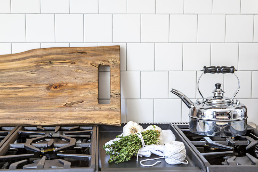 square subway tile kitchen range with wooden feast board / heirloomed