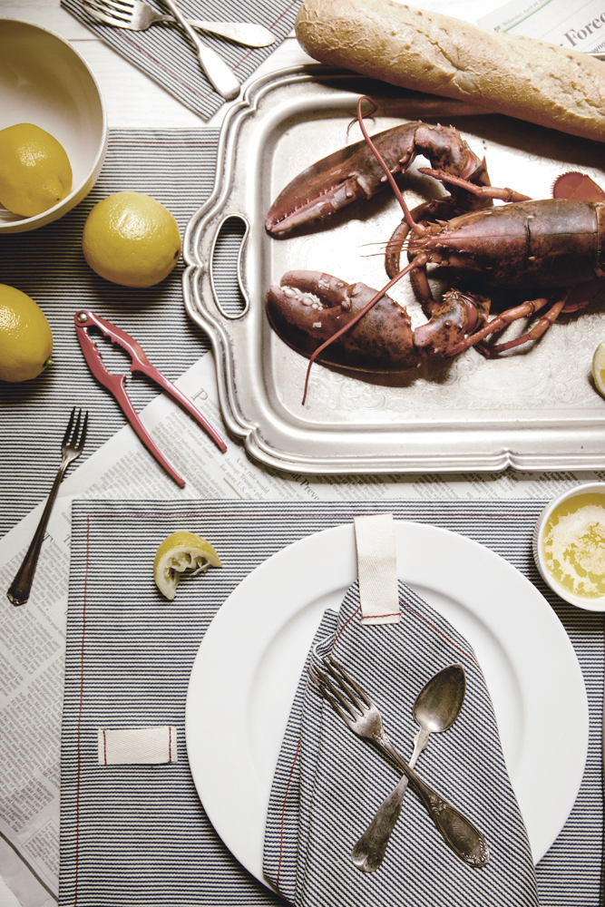 lobster dinner with fresh lemons and railroad stripe napkins / heirloomed