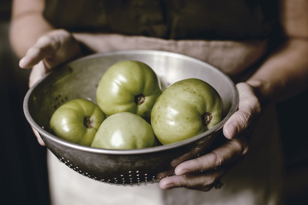 fresh green tomatoes in vintage colander / heirloomed