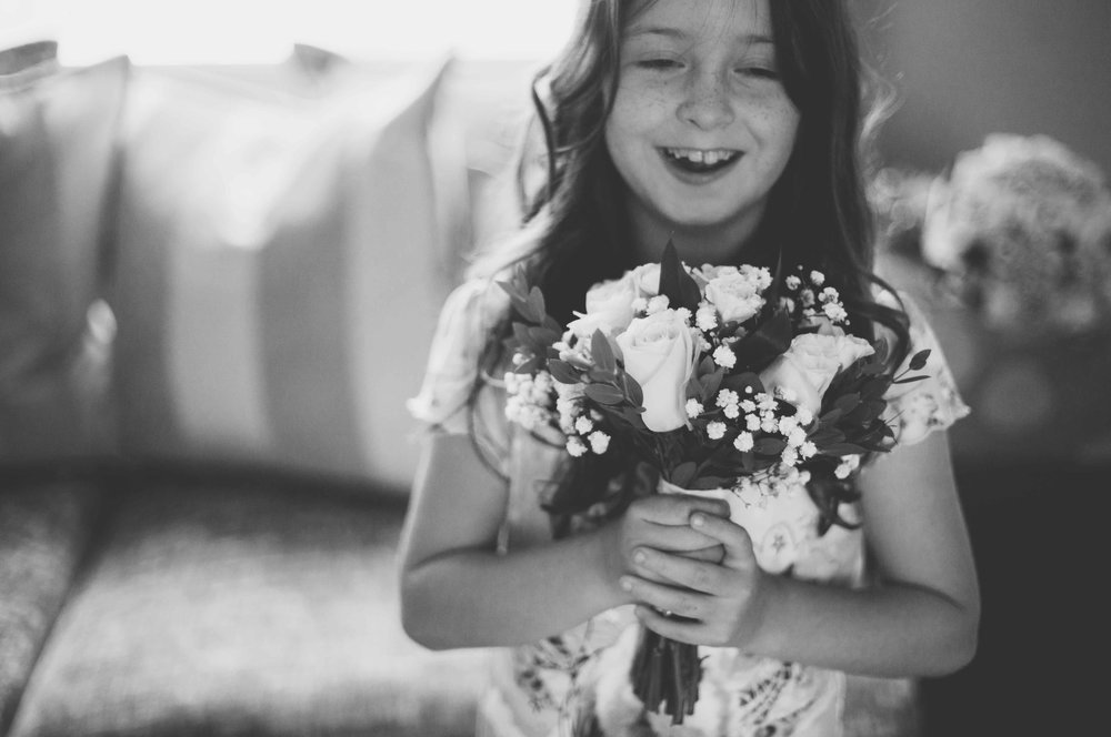 Flower girl with brides flowers smiling