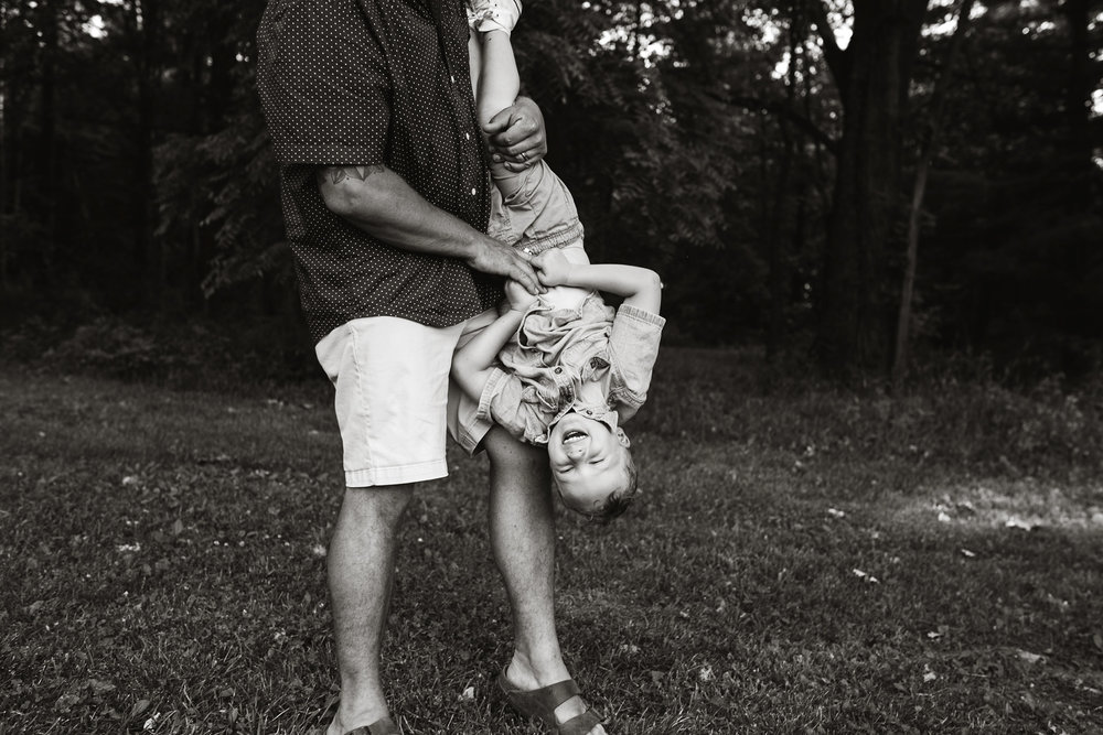 flynn-family-dad-holding-son-upside-down-laughing-jester-park-iowa-raelyn-ramey-photography.jpg