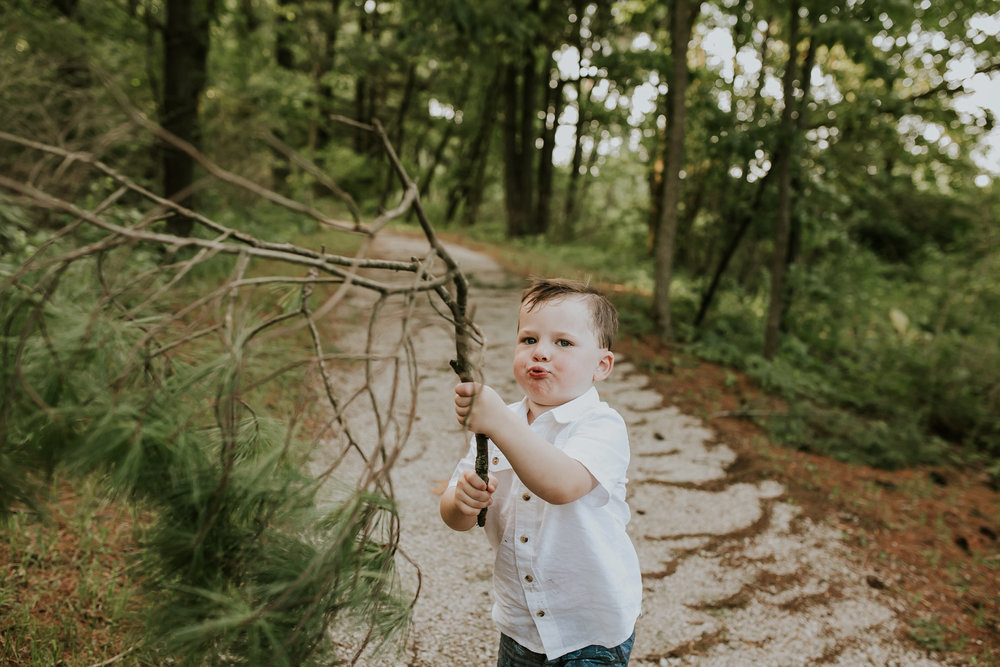 flynn-family-kid-holding-tree-branch-jester-park-iowa-raelyn-ramey-photography.jpg