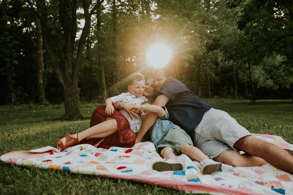 flynn-family-laying-on-blanket-with-sun-shining-jester-park-iowa-raelyn-ramey-photography.jpg