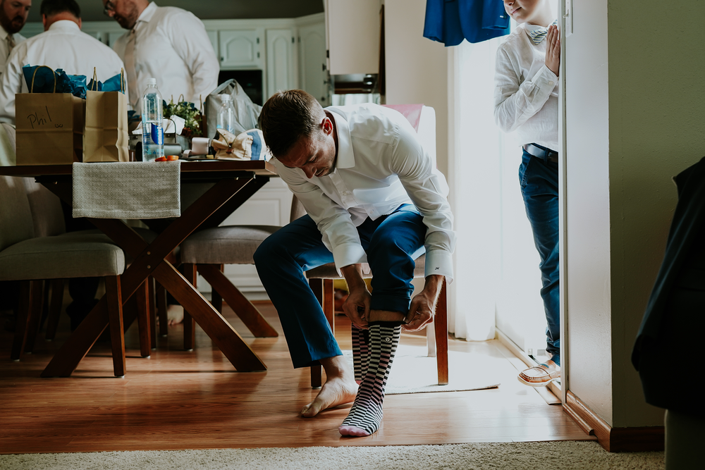 mr-mrs-hull-groom-putting-socks-on-desmoines-iowa-raelyn-ramey-photography-107.png