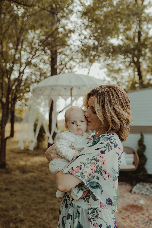 vintage-camper-mini-sessions-mom-holding-newborn-and-kissing-baby-iris-aisle-winterset-iowa-raelyn-ramey-photography-47.jpg