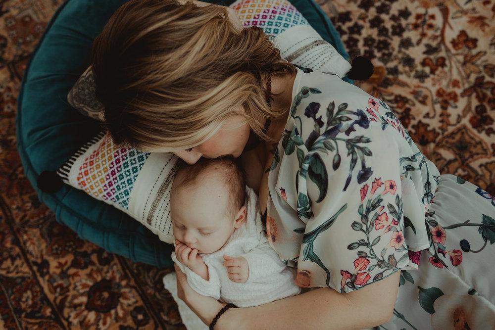vintage-camper-mini-sessions-mom-laying-with-newborn-on-rug-iris-aisle-winterset-iowa-raelyn-ramey-photography-13.jpg