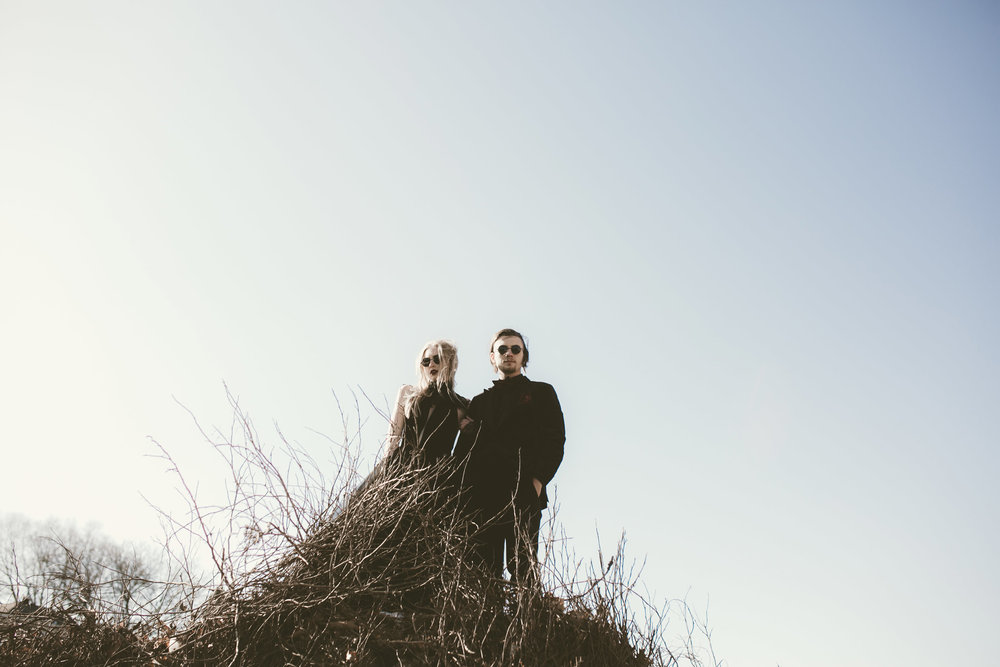 couple-standing-on-hill-black-wedding-dress-round-sunglasses-burlington-iowa-gothic-wedding-elopement-raelyn-ramey-photography-244.jpg