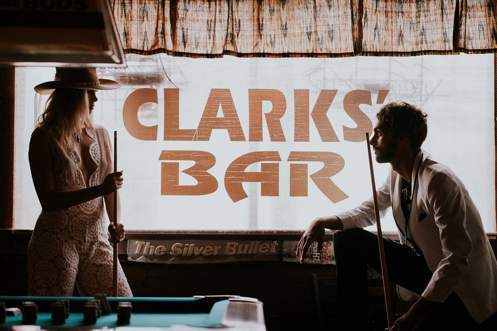 bride-groom-playing-pool-standing-in-front-of-clarks-bar-window-iowa-road-trip-romance-wedding-raelyn-ramey-photography-64.jpg