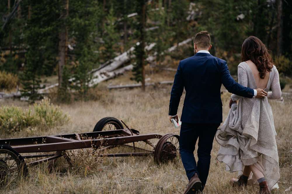 bride-and-groom-walking-to-sign-marriage-certificate-in-woods-double-a-barn-grand-lake-colorado-raelyn-ramey-photography-472.jpg