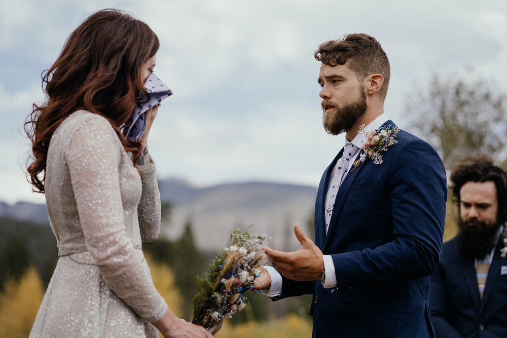bride-crying-while-groom-reads-vows-double-a-barn-grand-lake-colorado-raelyn-ramey-photography-436.jpg