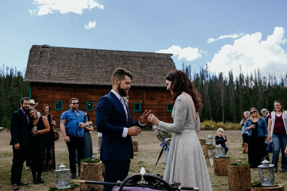 bride-putting-wedding-ring-on-groom-double-a-barn-grand-lake-colorado-raelyn-ramey-photography-445.jpg