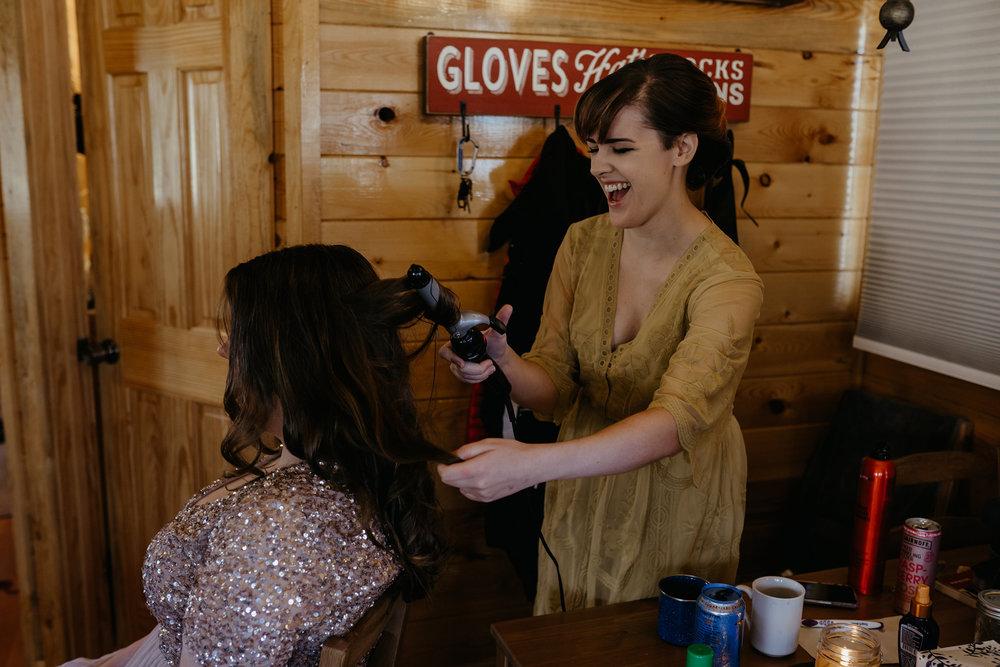 bridesmaid-doing-hair-laughing-lupine-village-grand-lake-colorado-raelyn-ramey-photography-19.jpg