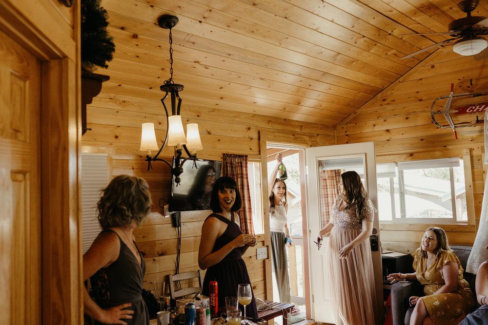 bridesmaid-bringing-champagn-lupine-village-grand-lake-colorado-raelyn-ramey-photography-33.jpg