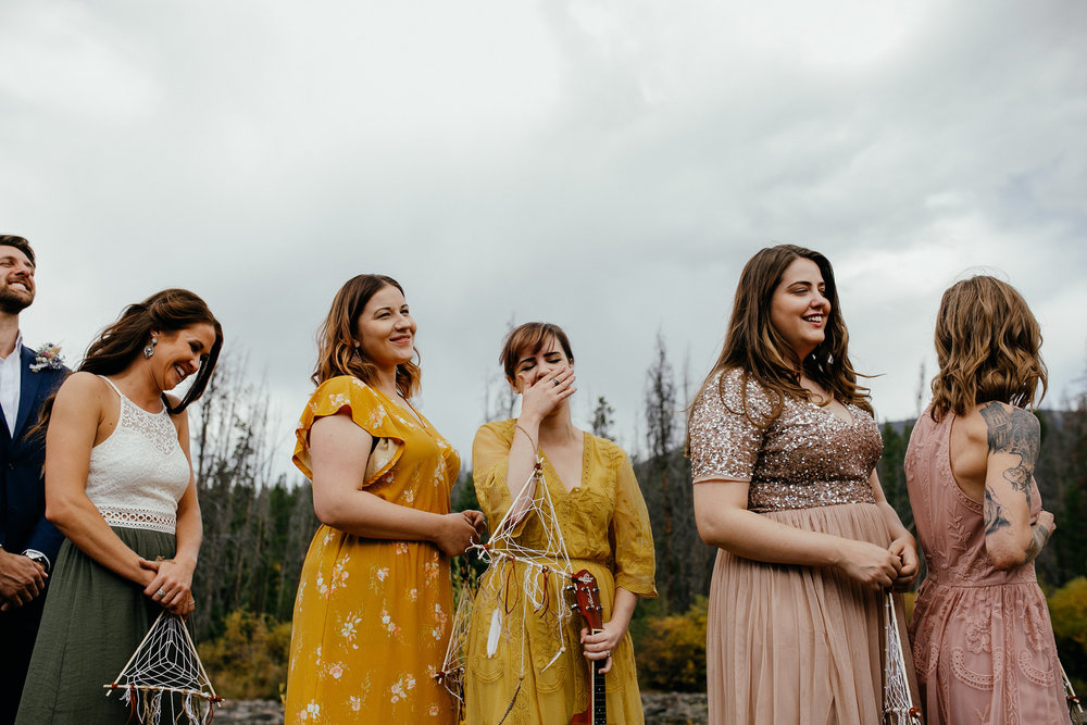 bridesmaids-laughing-during-ceremony-double-a-barn-grand-lake-colorado-raelyn-ramey-photography-442.jpg