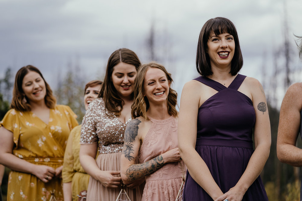 bridesmaids-laughing-during-ceremony-wedding-double-a-barn-grand-lake-colorado-raelyn-ramey-photography-428.jpg