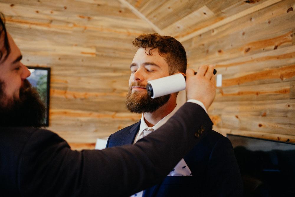 groom-getting-beard-lent-rolled-lupine-village-double-a-barn-grand-lake-colorado-raelyn-ramey-photography-113.jpg