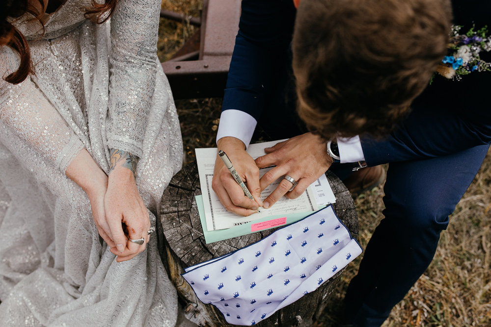 groom-signing-marriage-certificate-double-a-barn-grand-lake-colorado-raelyn-ramey-photography-475.jpg