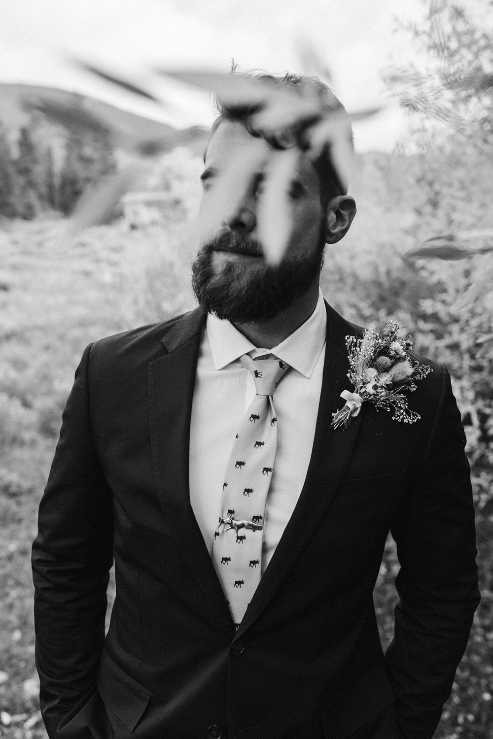 groom-with-leaves-in-front-of-eyes-double-a-barn-grand-lake-colorado-raelyn-ramey-photography-519.jpg