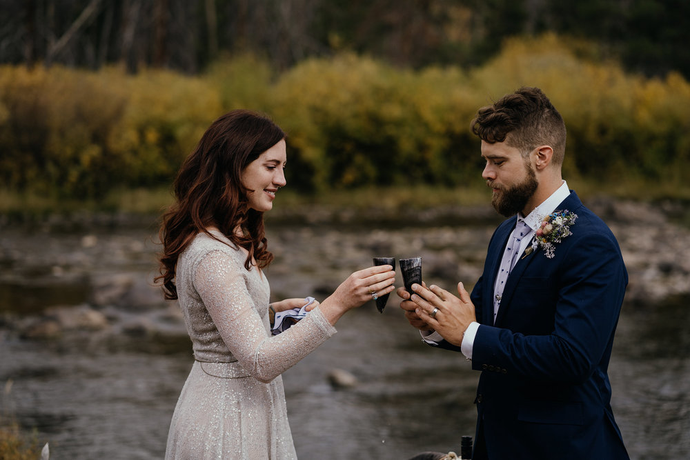 wedding-couple-toasting-during-ceremony-double-a-barn-grand-lake-colorado-raelyn-ramey-photography-453.jpg