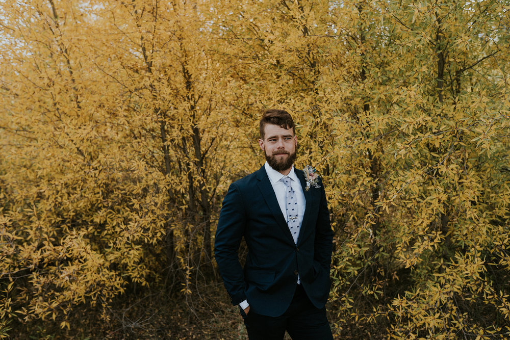 groom-standing-in-front-of-yellow-leaves-double-a-barn-grand-lake-colorado-raelyn-ramey-photography-518.jpg