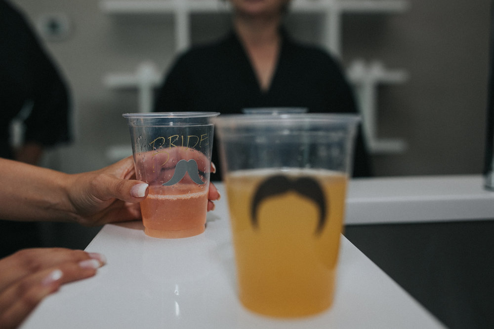 bride-drinking-cup-with-mustache-desmoines-iowa-ac-hotel-raelyn-ramey-photography.jpg