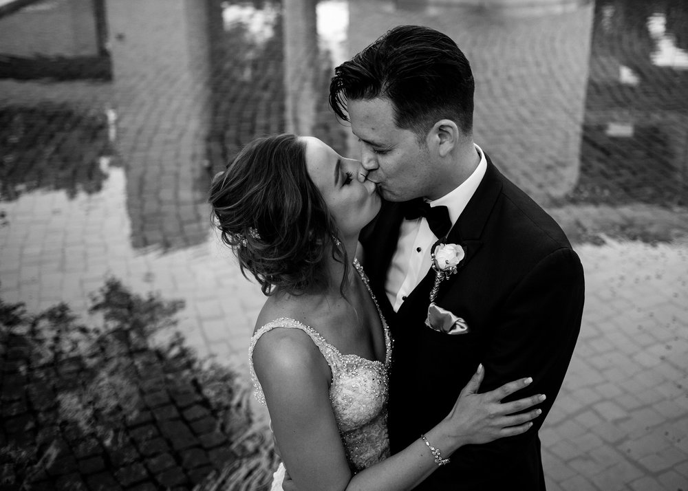bride-groom-kissing-with-fountain-water-in-background-desmoines-iowa-art-center-raelyn-ramey-photography.jpg