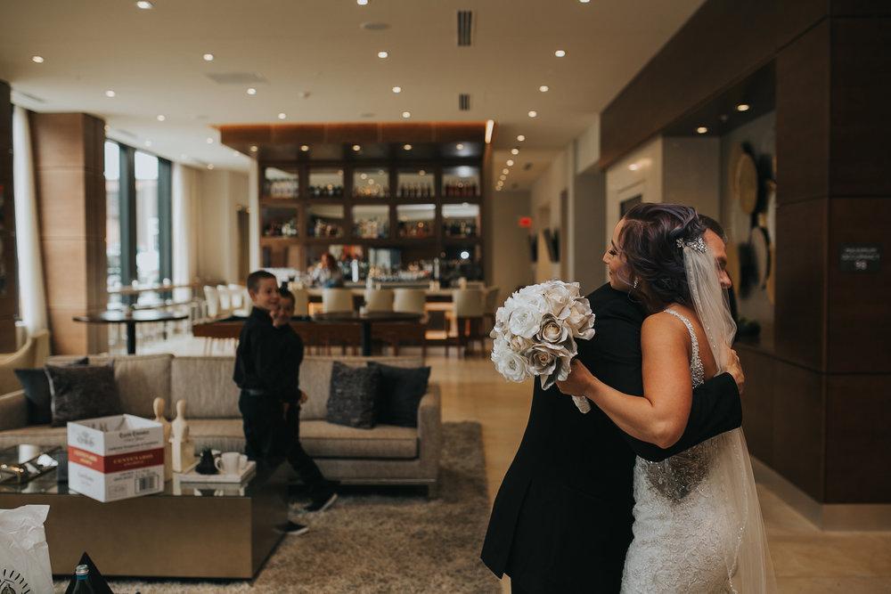 bride-hugging-father-lobby-desmoines-iowa-ac-hotel-raelyn-ramey-photography.jpg
