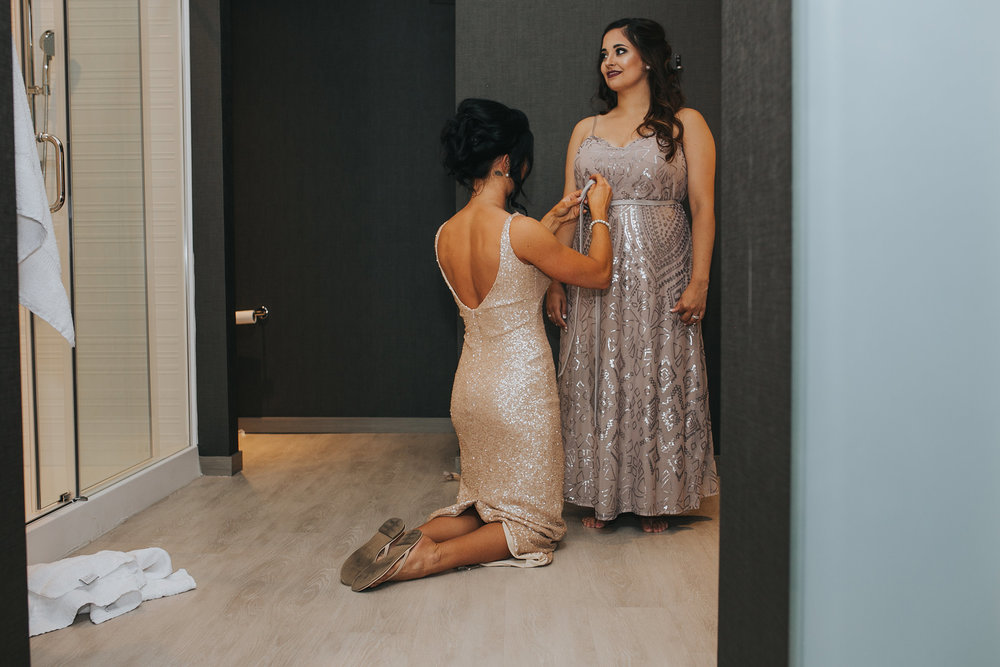 bridesmaids-helping-eachother-with-dresses-desmoines-iowa-ac-hotel-raelyn-ramey-photography.jpg